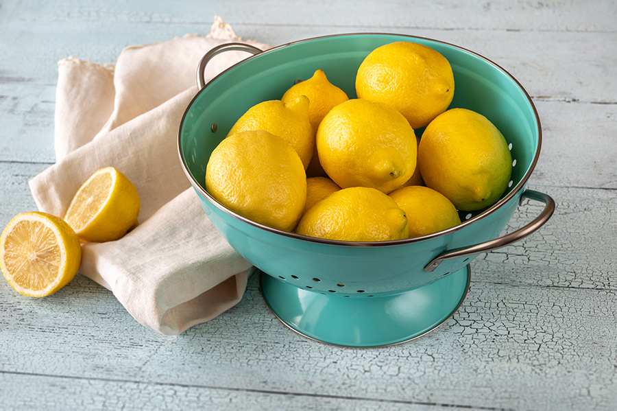Fresh lemons in blue colander. Wooden background